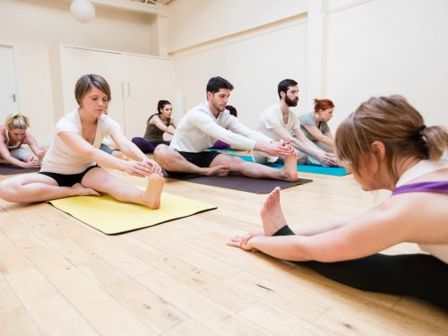 Trainer assisting group of people with stretching exercise in the fitness studio